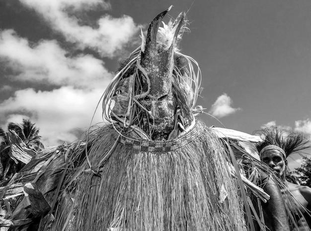 Strijder van de stam asmat in het kostuum van een boze geest danst een rituele dans.