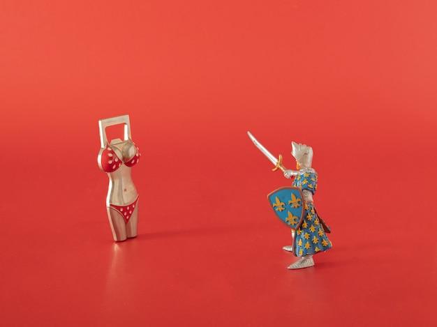 Strijdersstuk speelgoed tegen flesopener op de rode achtergrond. abstracte moderne vintage kunst.