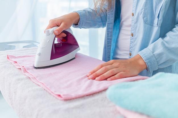 Strijken van linnen en kleding na het wassen op de strijkplank