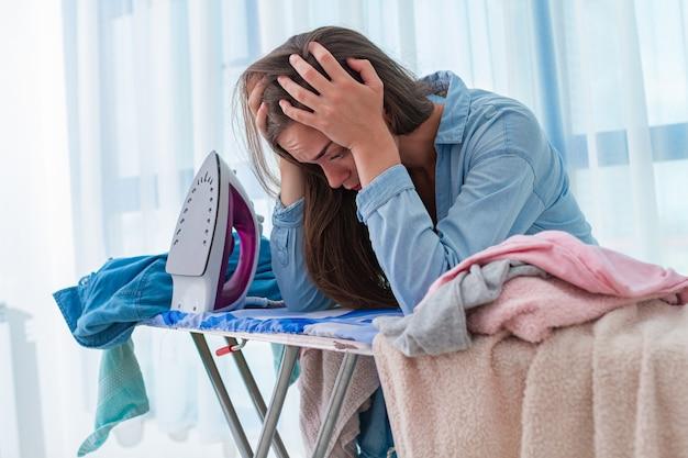Strijkende vrouw voelt zich moe van het strijken van een stapel kleren