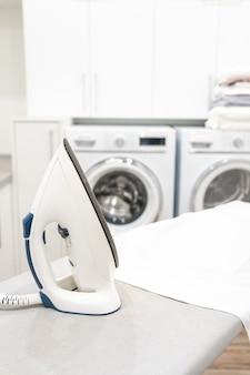 Strijkijzer op strijkplank met wit shirt in wasruimte