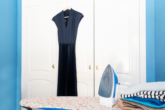 Strijkplank met strijkijzer en gevouwen kleding in de buurt van garderobe, huishouden en huiswerkconcept