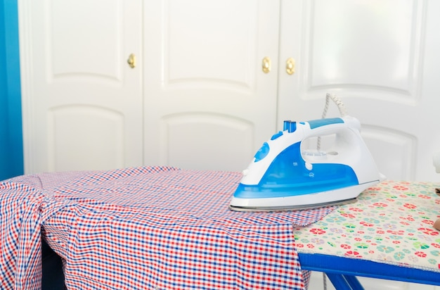 Strijkplank met strijkijzer en overhemd, huishouden en huiswerkconcept