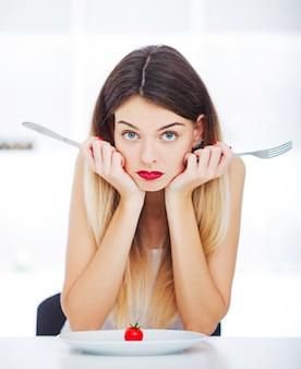 Strikt dieet. de handen die van de vrouw weinig kersentomaat op witte plaat proberen te snijden.