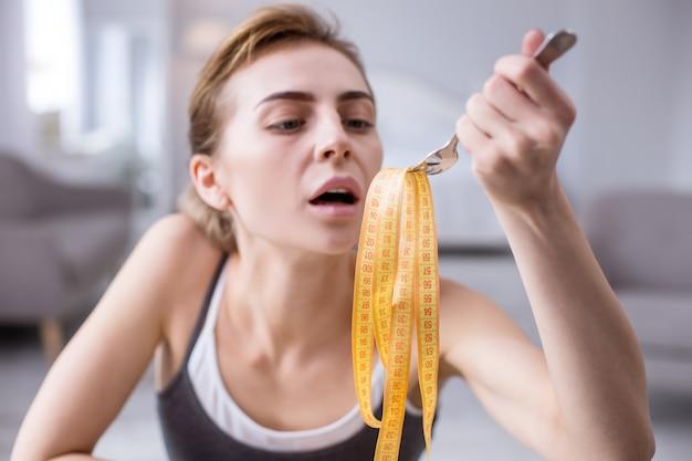 Strikt dieet. selectieve focus van centimeter tape op de vork van een ongezellige ongelukkige vrouw