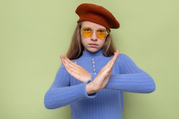 Strikt gebaar van geen mooi klein meisje dat een hoed met een bril draagt