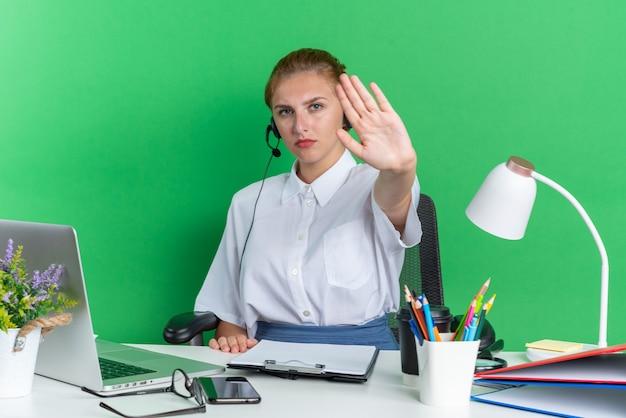 Strikt jong blond callcentermeisje met een hoofdtelefoon die aan het bureau zit met uitrustingsstukken die een stopgebaar doen