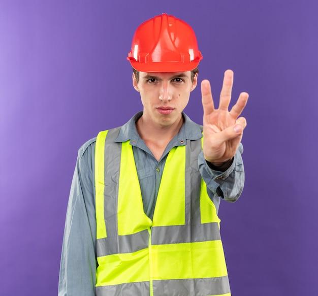 Strikt kijken naar camera jonge bouwer man in uniform met drie