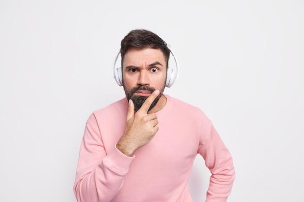 Strikt serieuze man houdt kin vast kijkt aandachtig, gefocust op iets luistert audioboek via draadloze koptelefoon gekleed in casual trui