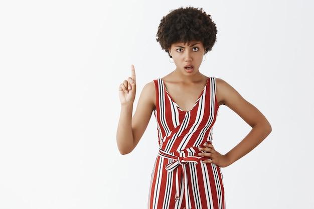 Strikte en bazige aantrekkelijke vrouwelijke werkgever met een donkere huid in gestreepte overall met wijsvinger zwaaien in stop of weigering gebaar hand op heup te houden ontevreden en ernstig