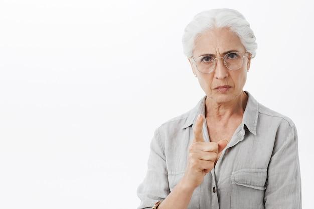 Strikte en boze oude dame die vinger schudt en fronst, scheldt persoon