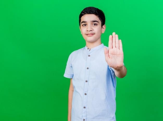 Strikte jonge blanke jongen die eindegebaar doet dat op groene muur met exemplaarruimte wordt geïsoleerd