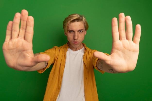 Strikte jonge blonde kerel die gele t-shirt draagt die handen opheft die op groen worden geïsoleerd