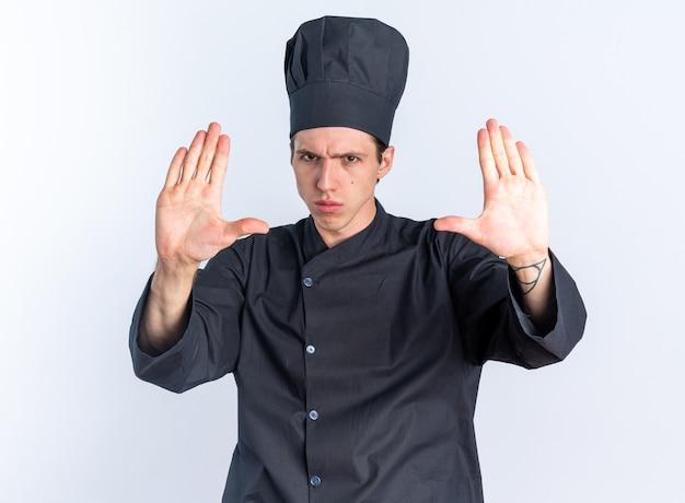 Strikte jonge blonde mannelijke kok in chef-kokuniform en pet die stopgebaar doet