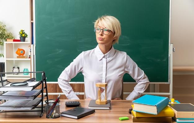 Strikte jonge blonde vrouwelijke leraar met een bril die aan het bureau zit met schoolbenodigdheden in de klas en de handen op de taille houdt en naar de zijkant kijkt