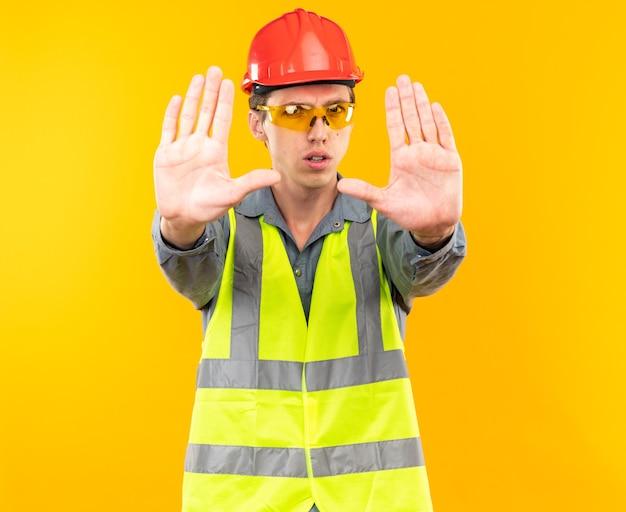 Strikte jonge bouwman in uniform met een bril die een stopgebaar toont