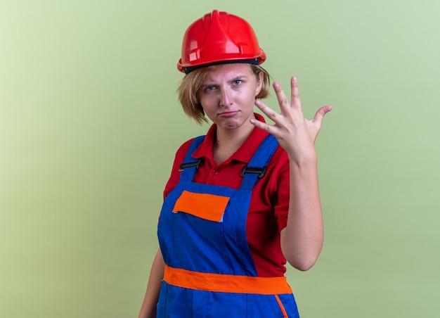 Strikte jonge bouwvrouw in uniform met vijf geïsoleerd op olijfgroene muur