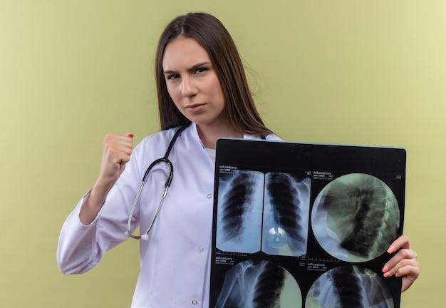 Strikte jonge dokter meisje dragen stethoscoop medische jurk x-ray houden op groene achtergrond