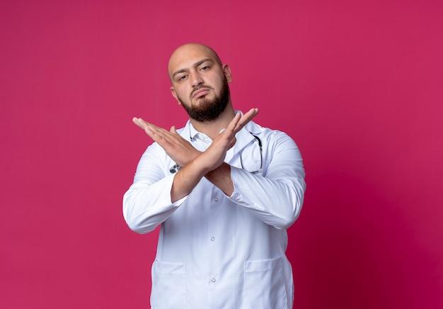 Strikte jonge kale mannelijke arts die medische mantel en stethoscoop draagt die gebaar van nee toont dat op roze wordt geïsoleerd