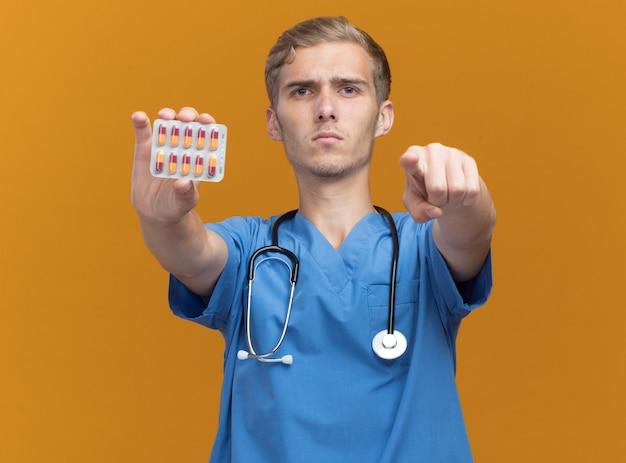 Strikte jonge mannelijke arts die artsenuniform met de pillen van de stethoscoopholding draagt die u gebaar tonen dat op oranje muur wordt geïsoleerd