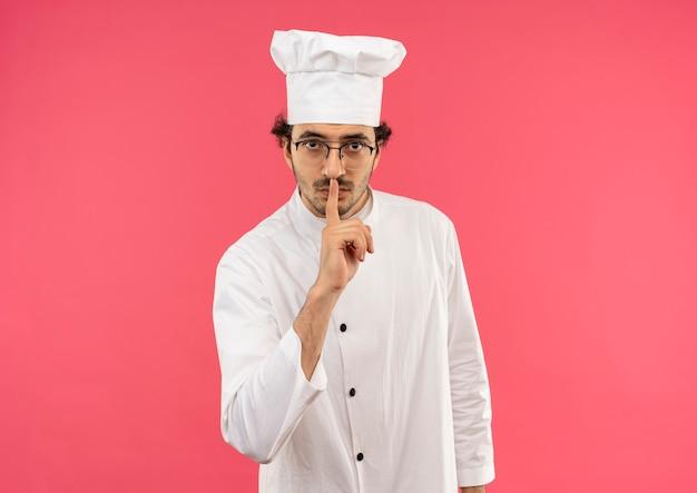 Strikte jonge mannelijke kok die eenvormige chef-kok en glazen draagt die stiltegebaar tonen dat op roze muur wordt geïsoleerd
