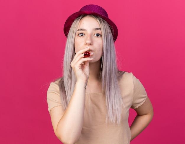 Strikte jonge mooie meid met feestmuts die feestfluitje blaast en hand op de heup zet geïsoleerd op roze muur