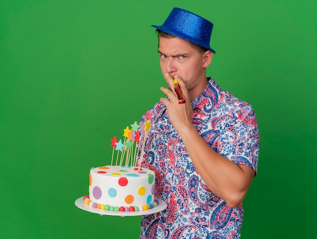 Strikte jonge partij kerel die blauwe hoed draagt ?? die cake houdt en blazende partijventilator die op groen wordt geïsoleerd