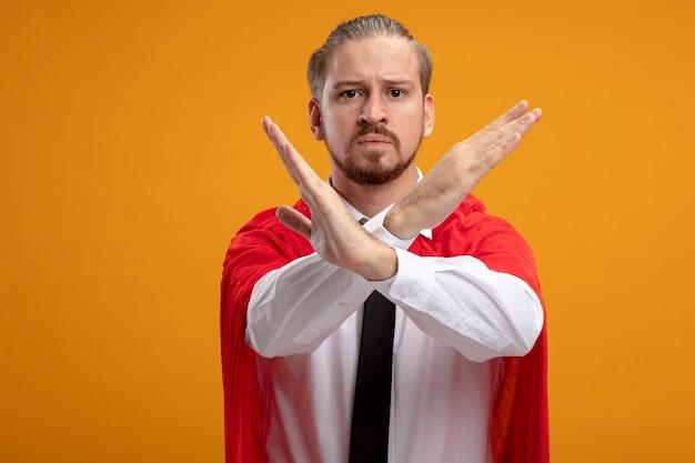 Strikte jonge superheld man kijken camera dragen stropdas weergegeven: gebaar van nee geïsoleerd op een oranje achtergrond