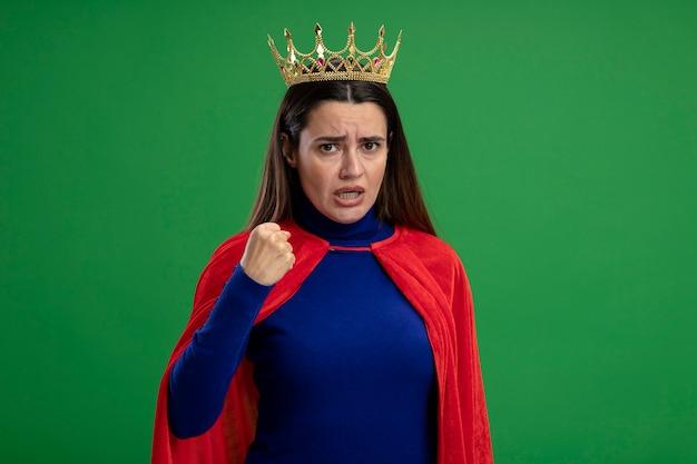Strikte jonge superheld meisje dragen kroon met vuist geïsoleerd op groen