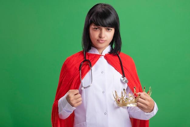Strikte jonge superheld meisje dragen stethoscoop met medische mantel en mantel houden kroon geïsoleerd op groene muur