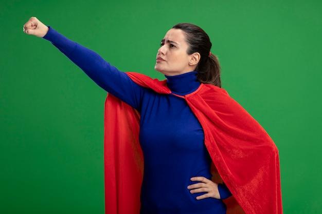 Strikte jonge superheld meisje kijken kant verhogen vuist geïsoleerd op groen