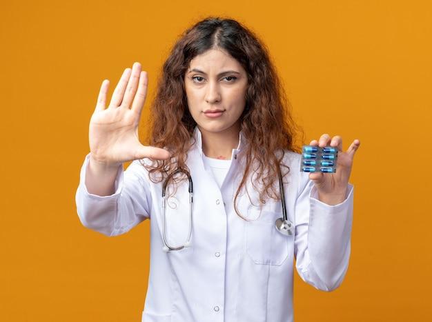 Strikte jonge vrouwelijke arts die een medisch gewaad en een stethoscoop draagt die een pakje medische capsules toont aan de camera die naar de voorkant kijkt en een stopgebaar doet dat op een oranje muur wordt geïsoleerd