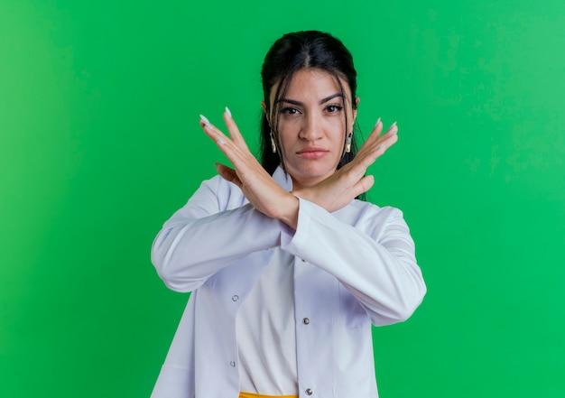Strikte jonge vrouwelijke arts die medische mantel draagt die geen gebaar doet dat op groene muur met exemplaarruimte wordt geïsoleerd