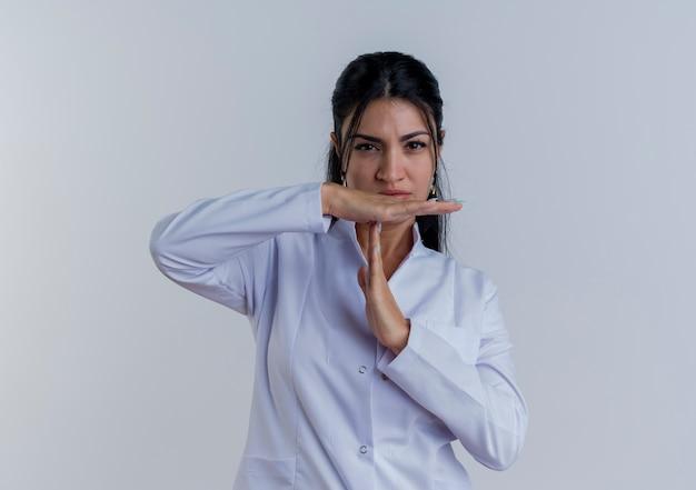 Strikte jonge vrouwelijke arts die medische mantel draagt die het doen geïsoleerde onderbrekingsgebaar kijkt