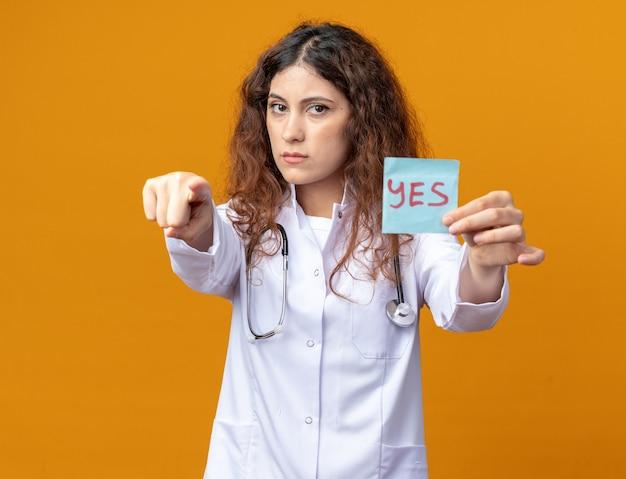 Strikte jonge vrouwelijke arts die medische mantel en stethoscoop draagt en naar voren wijst en zich uitstrekt ja notitie naar camera geïsoleerd op oranje muur
