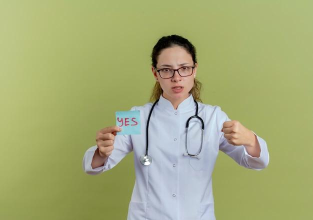Strikte jonge vrouwelijke arts die medische mantel en stethoscoop met bril draagt die document nota houdt die geïsoleerde vuist toont