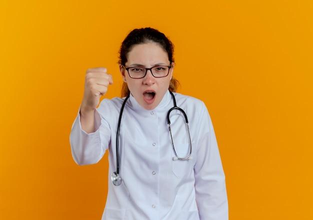 Strikte jonge vrouwelijke arts die medische robe en stethoscoop met glazen draagt die geïsoleerde vuist standhoudt