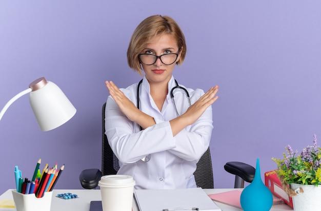 Strikte jonge vrouwelijke arts met een medisch gewaad met een stethoscoop en een bril zit aan tafel met medische hulpmiddelen die een gebaar van nee tonen geïsoleerd op blauwe achtergrond