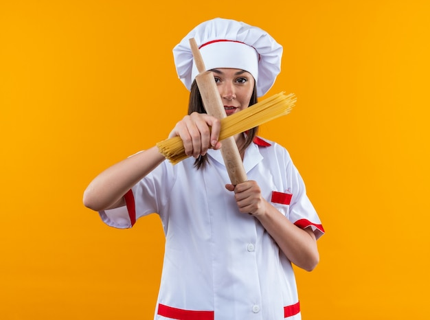 Strikte jonge vrouwelijke kok die een uniform van de chef-kok draagt en spaghetti kruist met deegroller geïsoleerd op een oranje muur