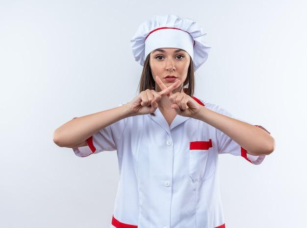 Strikte jonge vrouwelijke kok in uniform van de chef-kok met gebaar van nee geïsoleerd op een witte achtergrond