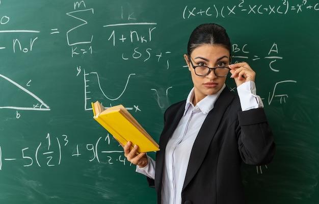Strikte jonge vrouwelijke leraar met een bril die vooraan op het schoolbord staat met een boek in de klas