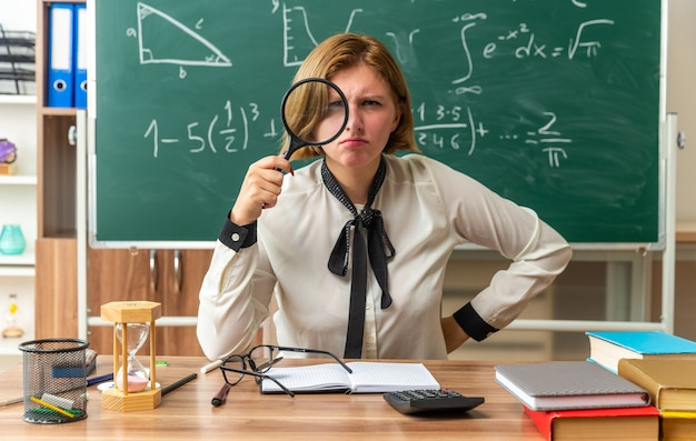 Strikte jonge vrouwelijke leraar zit aan tafel met schoolbenodigdheden en kijkt naar voren met vergrootglas hand op heup in klaslokaal
