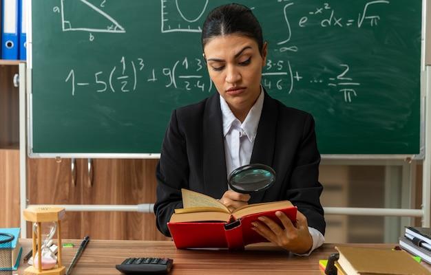 Strikte jonge vrouwelijke leraar zit aan tafel met schoolbenodigdheden leesboek met vergrootglas in de klas