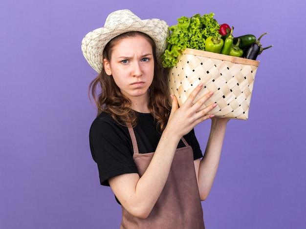 Strikte jonge vrouwelijke tuinman die een tuinhoed draagt met een groentemand op de schouder