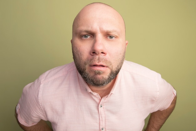 Strikte kale man van middelbare leeftijd met roze t-shirt