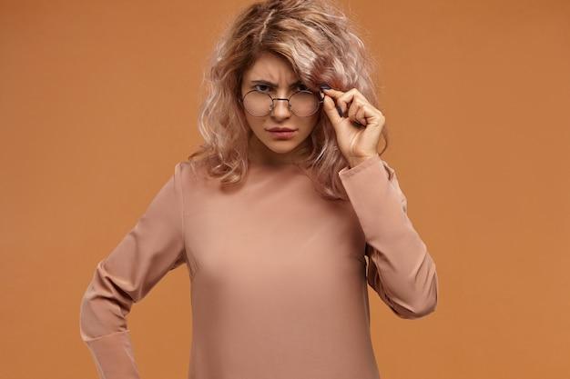 Strikte modieuze vrouwelijke leraar brillen verlagen en camera staren met ontevreden gezichtsuitdrukking, wachtend op antwoord