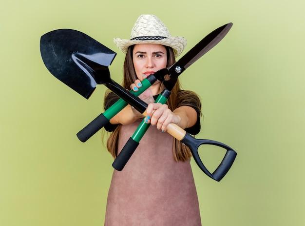 Strikte mooie tuinman meisje in uniform dragen tuinieren hoed bedrijf en kruising tondeuse met schop geïsoleerd op olijfgroene achtergrond