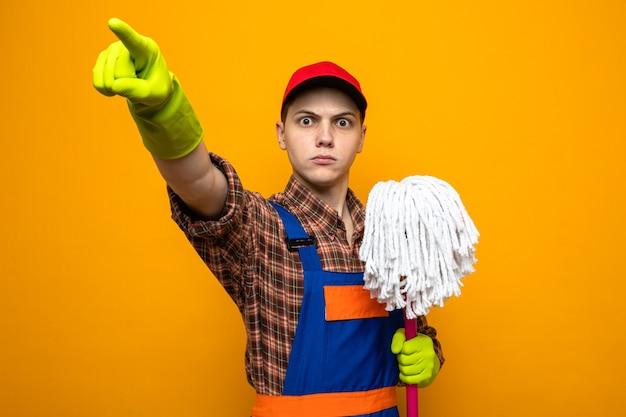 Strikte punten aan de voorkant van een jonge schoonmaakster die uniform en pet draagt met handschoenen die dweil vasthouden