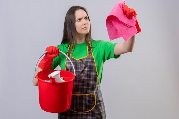 Strikte schoonmaak jong meisje dragen uniform in rode handschoenen houden schoonmaak gebaar kijken naar vod aan kant op geïsoleerde witte achtergrond