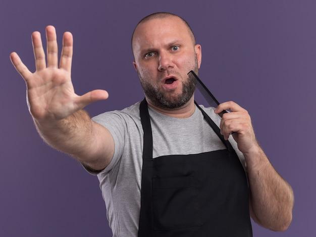 Strikte slavische mannelijke kapper van middelbare leeftijd in uniforme baard kammen met stop gebaar geïsoleerd op paarse muur